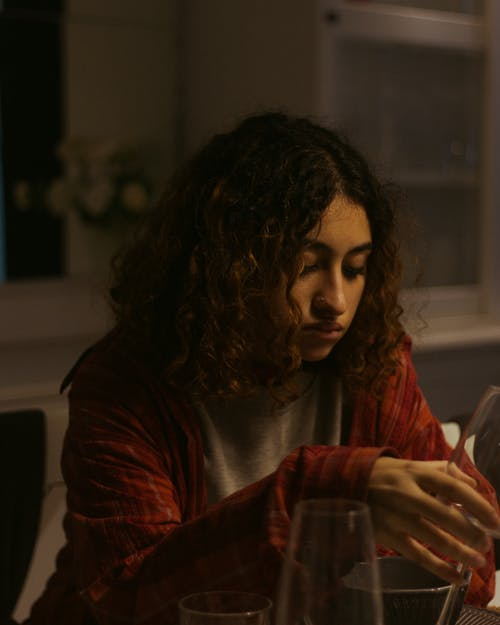 Sad young ethnic woman in casual clothes sitting at table with glasses in light flat