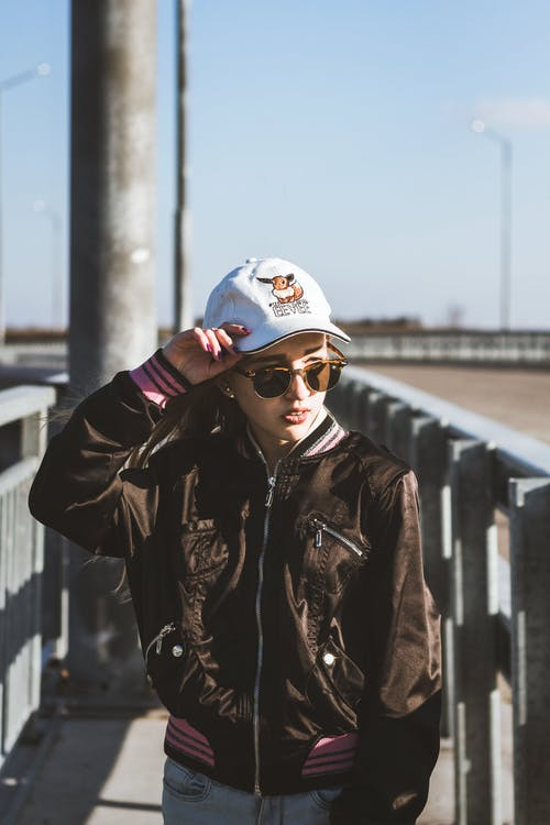 Young stylish female wearing stylish outfit and sunglasses standing with hand on head near metal railing and looking away
