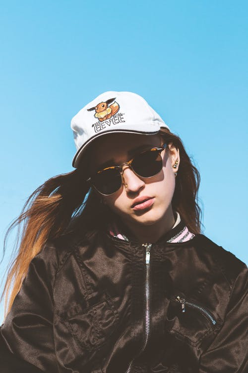 Low angle of serious female in stylish sunglasses and cap with flying hair against blue cloudless sky