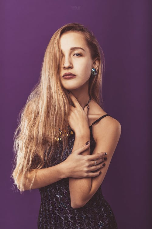 Alluring woman with long hair standing in studio