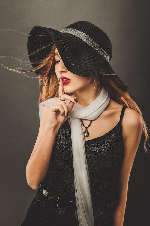Female with long flying hair wearing trendy hat and scarf touching lips with forefinger while making shh gesture in studio