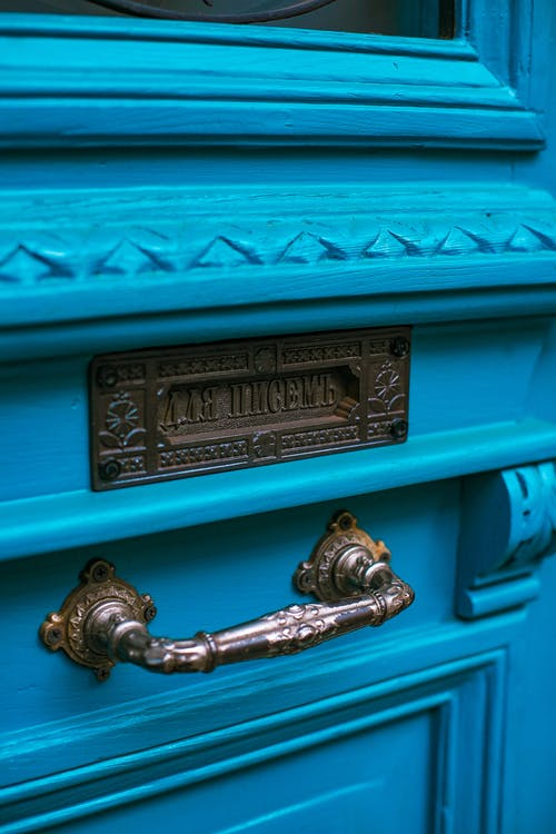 Closeup of old fashioned entrance door with carved wooden surface and bronze door handle with metal ornamented mailbox with inscription in Cyrillic