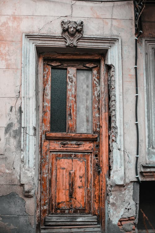 Exterior of old weathered stone building with decorative elements and wooden door in town street in daylight