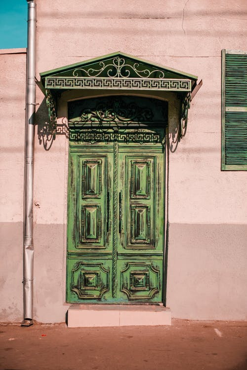 Pink stone building facade with decorative elements near pipe and shabby green door in town street in sunny day
