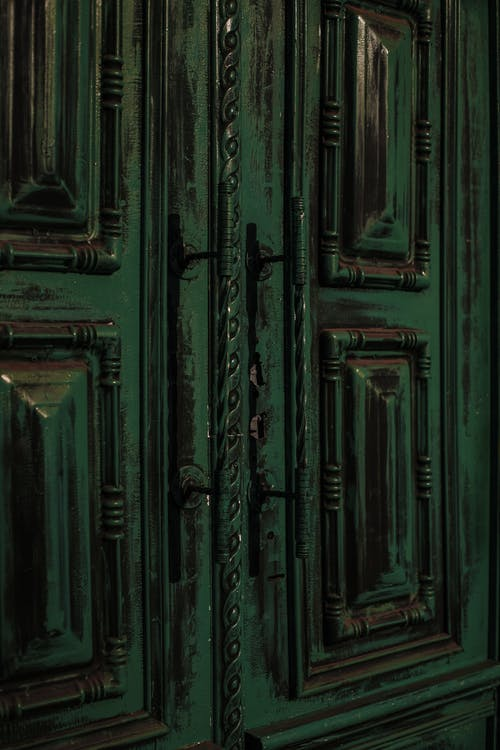 Vintage weathered door with ornamental elements and handles