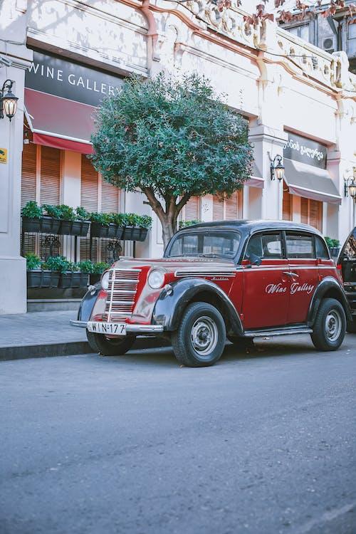 Retro car parked on street near modern buildings
