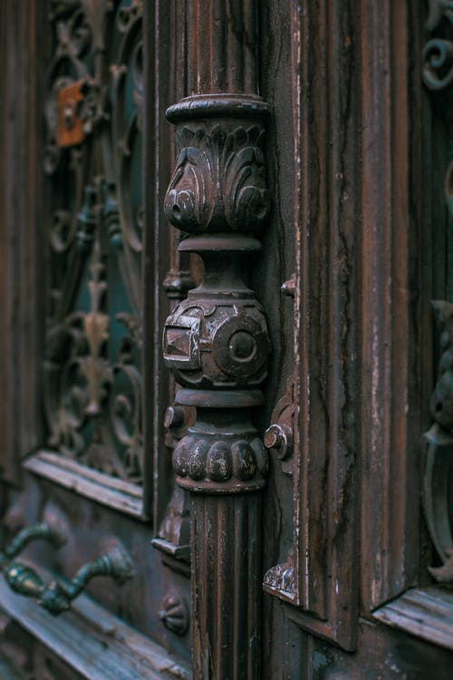 Old wooden door of aged building with metal handle and decorative elements