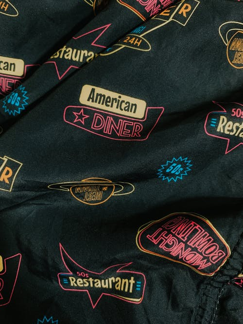 Details of trendy cotton shirt with colorful retro styled inscriptions and logos of American diners