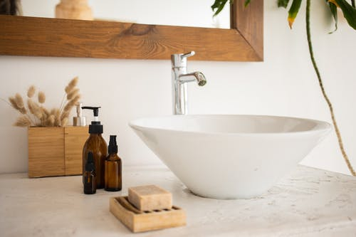 Interior of bathroom table with soap and cosmetic oil placed near white sink and faucet under mirror in wooden frame in modern apartment