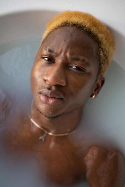 Black man with dyed hair lying in bathtub
