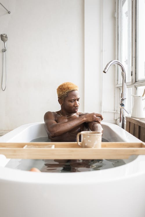 African American man sitting in bathtub with cup of coffee on tray and scrubbing arms with sponge and soap