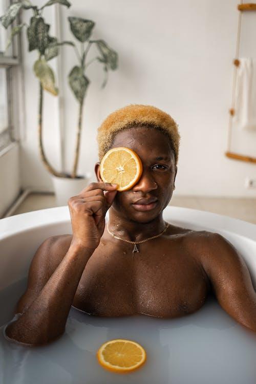 Black man with fresh slice of orange in bath