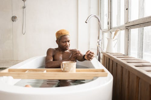 Young African American guy sitting in bathtub and washing body
