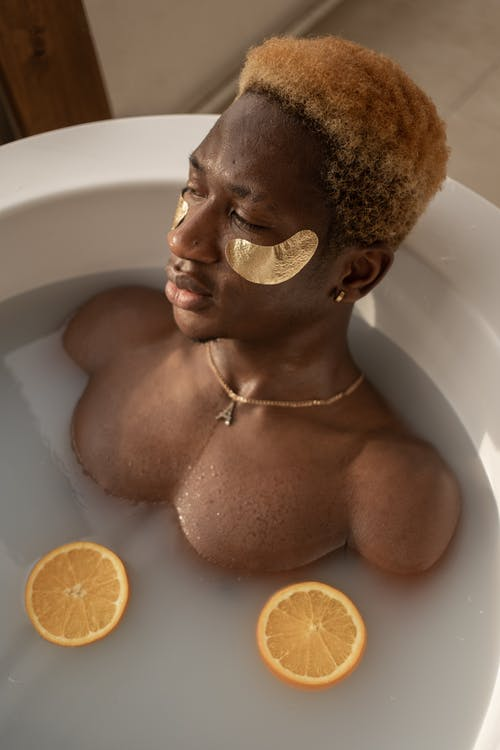From above of young shirtless metrosexual man with dyed hair and eye patches recreating in water with sliced oranges during spa procedure
