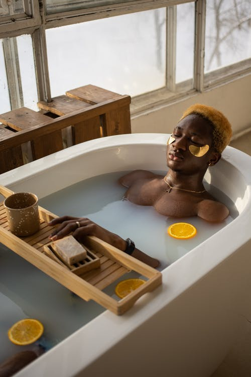 Black man with eye patches lying in bath during spa procedure