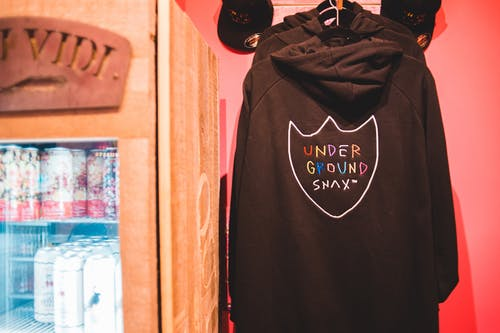 Trendy hoodies and fridge with refreshing drinks in shop