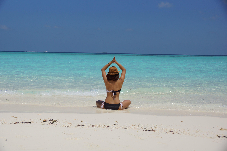 Woman in Black and White Bikini Taking Up Yoga Near Seashore during Daytime