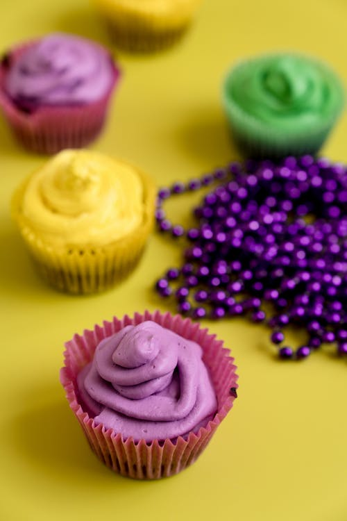 Colorful Cupcakes And Purple Beads On Yellow Background
