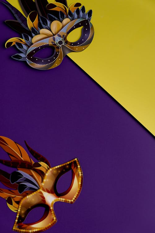 Mardi Gras Masks On Yellow And Purple Background