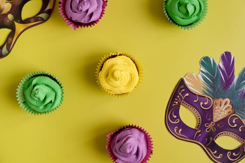 Colorful Cupcakes And Masks On Yellow Backg