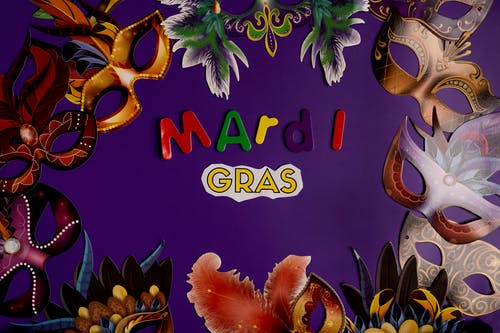 Colorful Masks And Mardi Gras Text On Purple Background