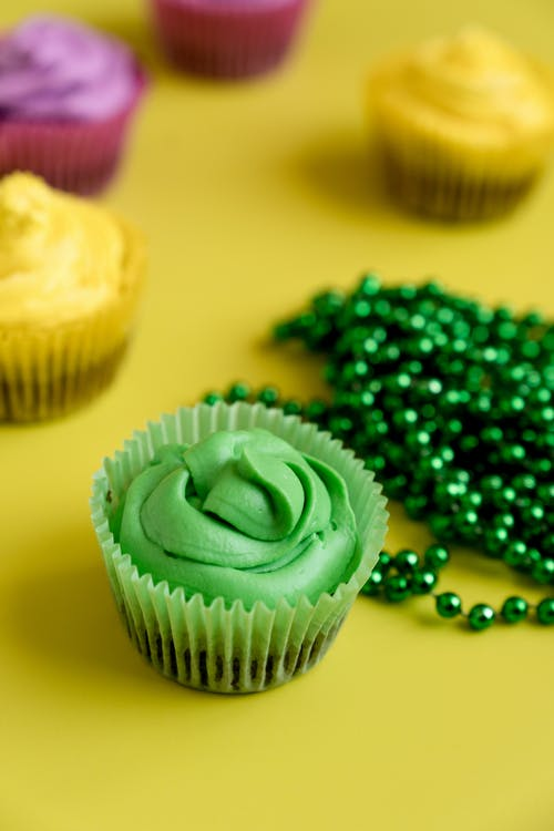 Colorful Cupcakes And Green Beads On Yellow Background