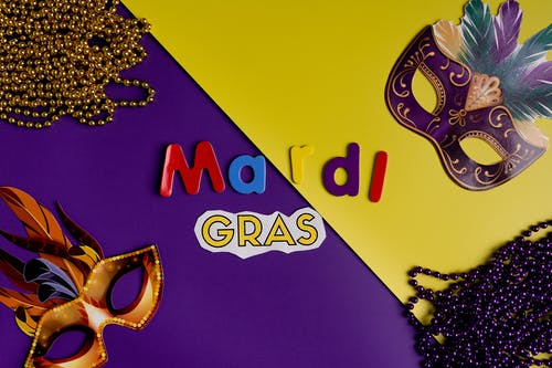 Masks And Beads On Yeloow And Purple Background