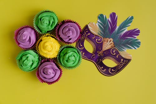 Colorful Cupcakes And Mask On Yellow Background
