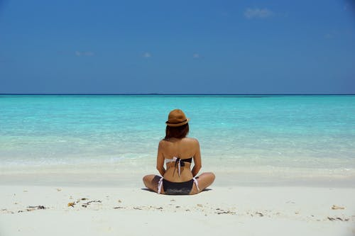 Woman Wearing Black and White Brassiere Sitting on White Sand