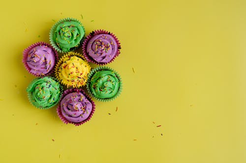 Colorful Cupcakes On Yellow Background