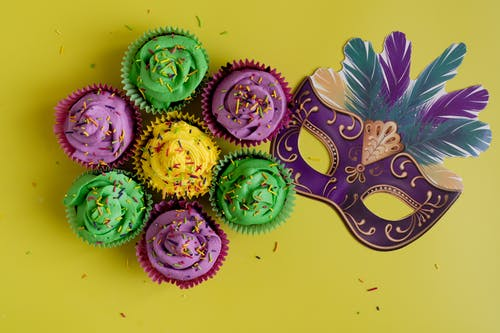 Colorful Pastries And Mask On Yellow Background