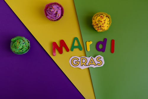 Mardi Gras Text And Cupcakes On Colorful Background