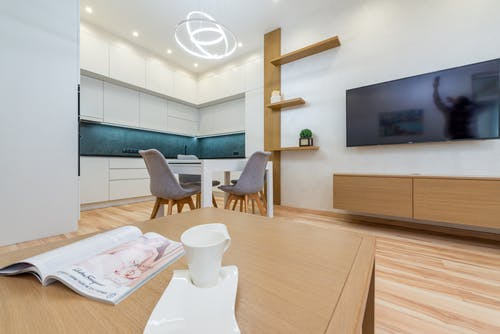 Interior of modern light room with table with mug and magazine in front of TV on wall next to chairs and open kitchen with cabinets and shelves