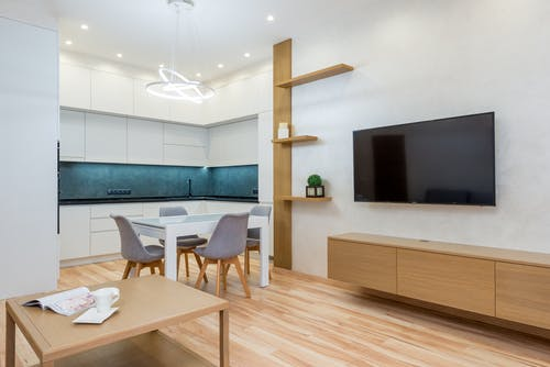 Dining table next to TV and kitchen near chairs