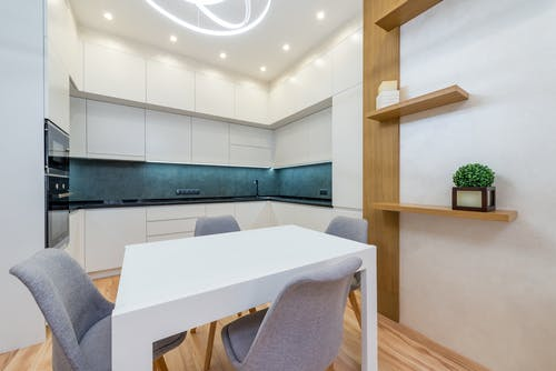 Modern apartment interior with table with chairs next to shelves and open kitchen with cabinets