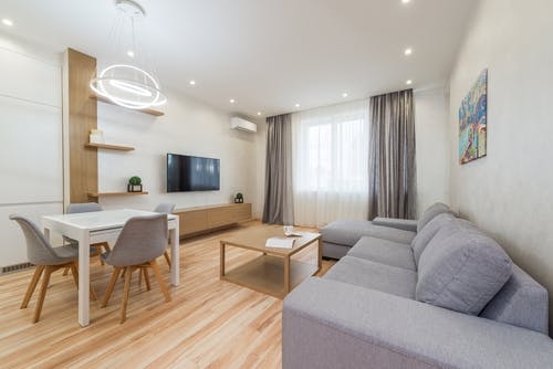 Apartment with sofa and table with chairs next to TV