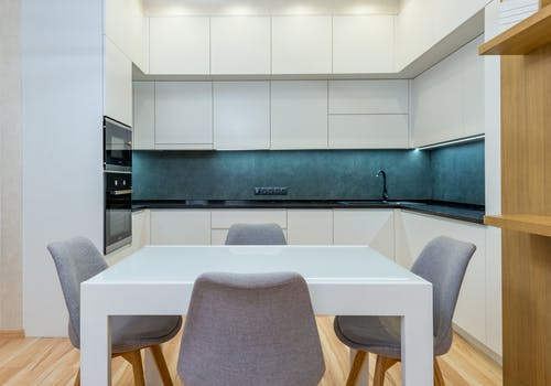 Apartment with table with chairs near open kitchen