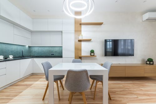 Modern flat interior with table with chairs next to shelves and TV on wall near open kitchen with cupboards