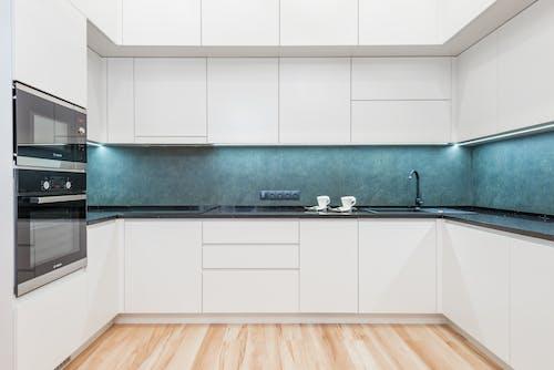 Interior of white modern kitchen with minimalist design of white cabinets blue backsplash and black built in appliances