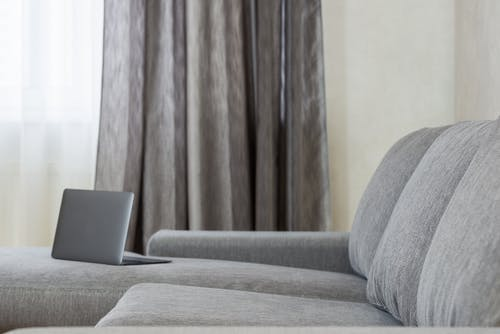 Laptop on gray sofa in living room