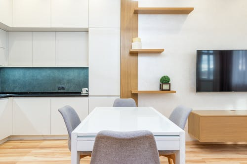 House with table with chairs next to kitchen and TV