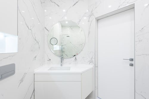Washroom interior with cabinet with sink and mirror near door