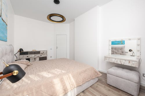 Light cozy bedroom with cosmetic mirror and pouf