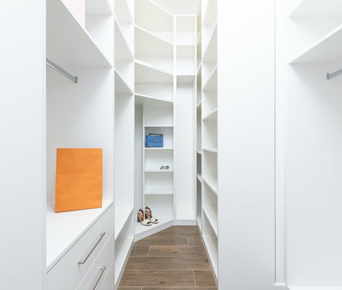 Perspective of white dressing room with rows of shelves and metal railings in modern design