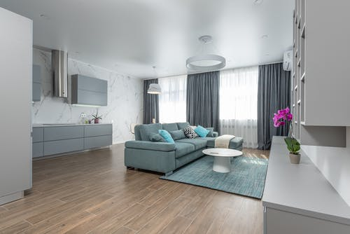 Interior of modern living room with comfortable sofa carpet and round table and open kitchen with cupboards in modern apartment