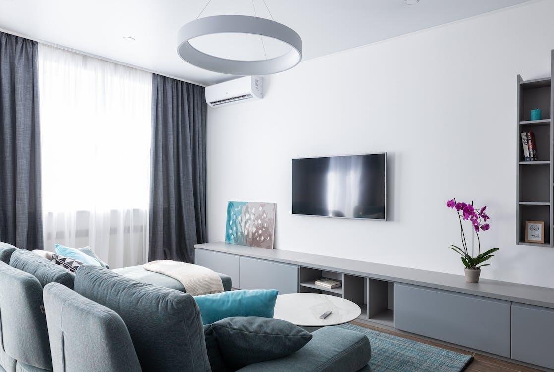 Sala de estar pintada de blanco con muebles grises y mesas de marmol