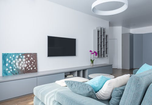 Modern interior of spacious living room decorated with gray shelves purple potted flower and picture