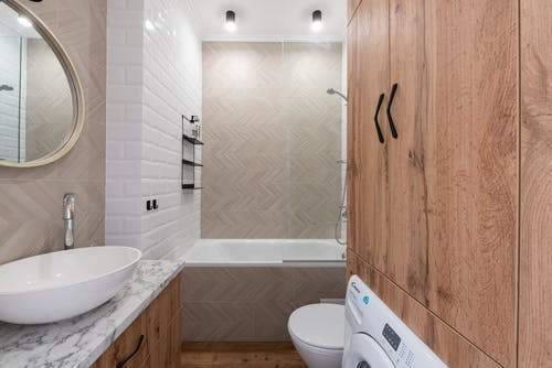 Contemporary bathroom with washing machine and oval shaped mirror