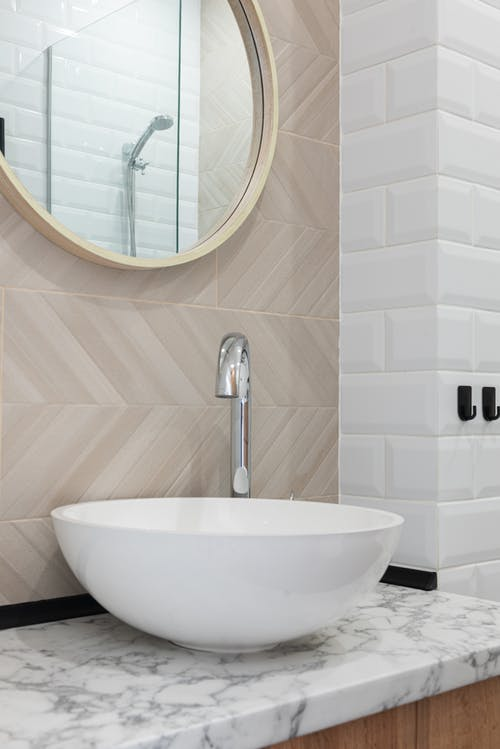 Interior of light modern restroom with sink and faucet on cabinet under mirror on tile wall