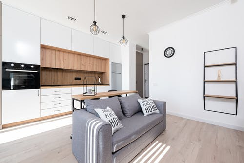 Interior of bright modern room with open kitchen with cupboards and oven next to couch with pillows and table